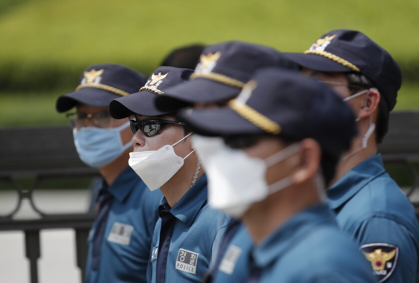 Police officers wearing face masks to help protect against the spread of the new coronavirus stand guard outside of the Supreme Court of Korea in Seoul, South Korea, Thursday, July 16, 2020. (AP Photo/Lee Jin-man)