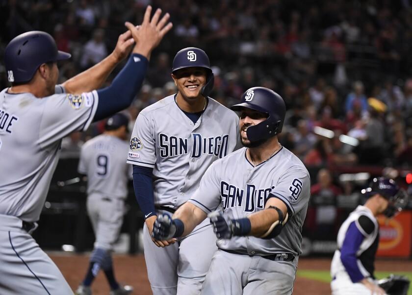 Austin Hedges celebrates with teammates Manny Machado, background, Hunter Renfroe after hitting a three run homer against the Diamondbacks on Thursday.