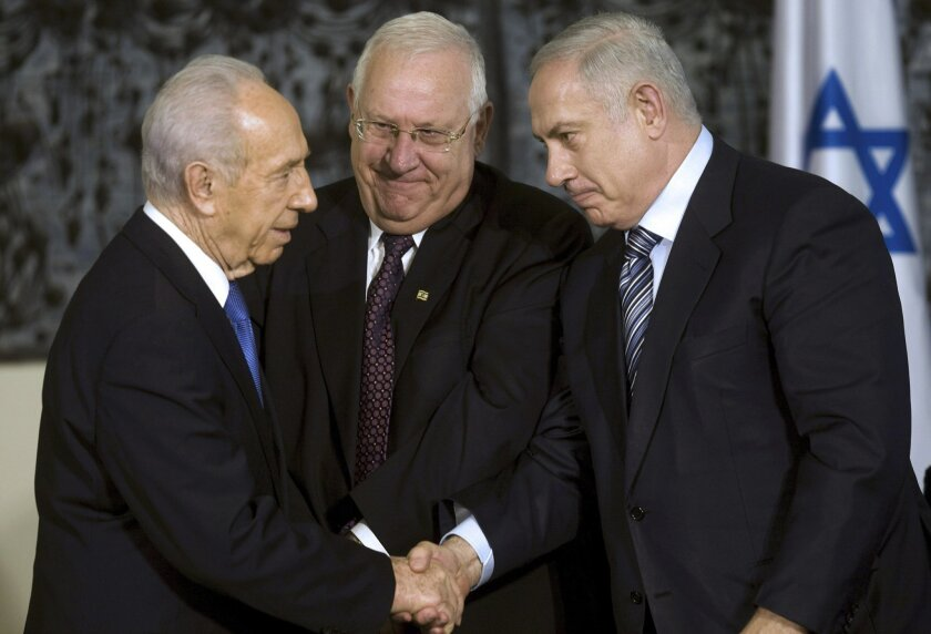 FILE - In this April 1, 2009, file photo, Israeli President Shimon Peres, left, greets Israeli Prime Minister Benjamin Netanyahu, right, as Knesset speaker Reuven Rivlin stands near during a handover ceremony at Peres' residence in Jerusalem. A nasty race to succeed Shimon Peres as Israel's head of state is finally coming to an end on Tuesday, June 10, 2014, with five candidates facing off in parliament over the right to become the country's next president. (AP Photo/Menahem Kahana, Pool, File)