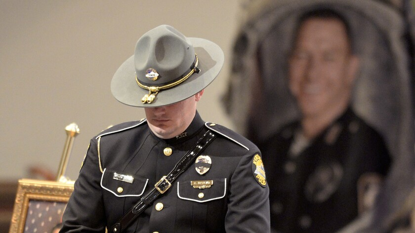 A Kentucky State Police officer stands as part of the honor guard during the funeral service for Bardstown, Ky., Officer Jason Ellis in May 2013.