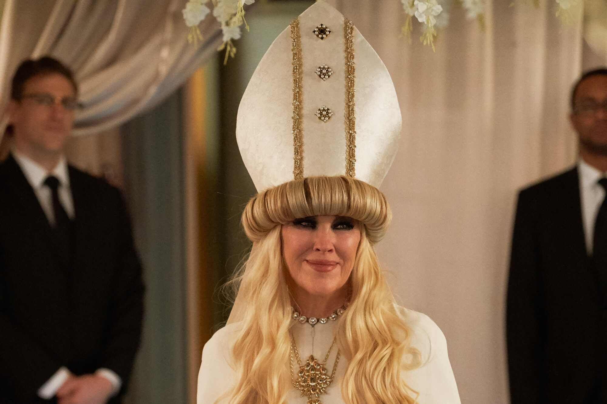 """Catherine O'Hara as Moira Rose, wearing an Alexander McQueen gown with a miter on """"Schitt's Creek."""""""