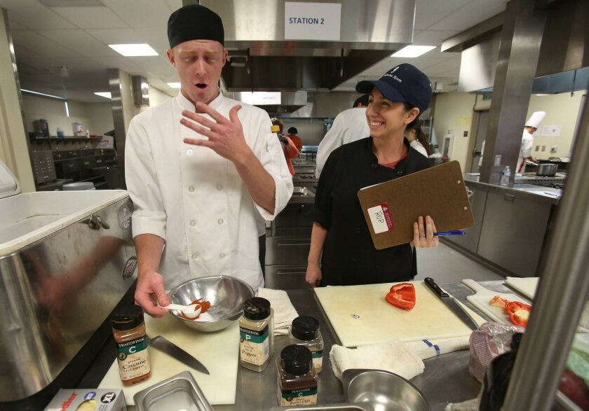 Escondido, CA. February 23, 2016 |   Cameron Wood, of San Dieguito Academy, tries not to sneeze after pouring several spices into a bowl, just as professional chef Robin Katz, with the Marine Room, asks him about his spice selection. North County high school students showed off their culinary skill