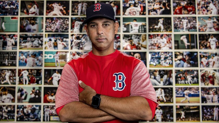 Alex Cora poses in front of a wall of photographs depicting every win throughout the season.