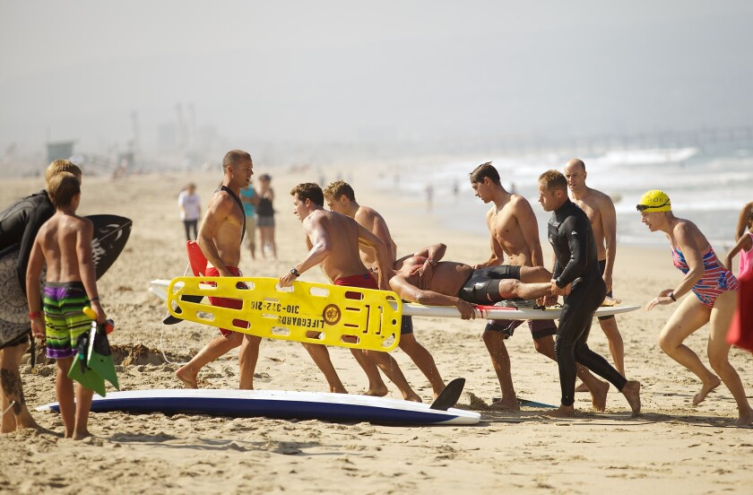 A swimmer bitten by a shark near the Manhattan Beach Pier is carried to safety on July 5.