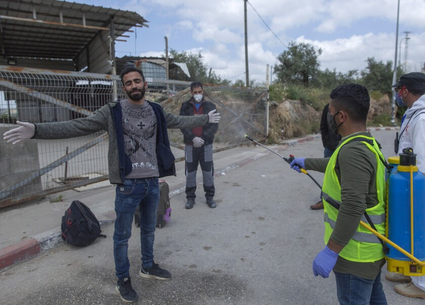 A paramedic sprays disinfectant on Palestinian laborers as they exit an Israeli army checkpoint April 7 near the West Bank village of Nilin.
