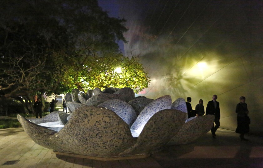 """Vistiors listen to artist Susan Philipsz's """"Prelude in the Form of a Passacaglia,"""" a sound installation in the garden behind Disney Hall."""
