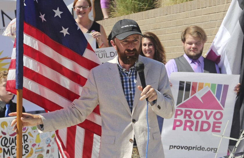 FILE - Utah County Commissioner Nathan Ivie speaks as he holds the American flag during a news conference on June 14, 2018, in Provo, Utah. Ivie, a Republican voted out of office in a primary after coming out as gay in conservative Utah says a backlash during campaign season has him questioning whether his party has a place for him. Ivie made national headlines more than a year ago when he publicly announced his orientation while serving as a county commissioner in deep-red Utah County. (AP Photo/Rick Bowmer, File)