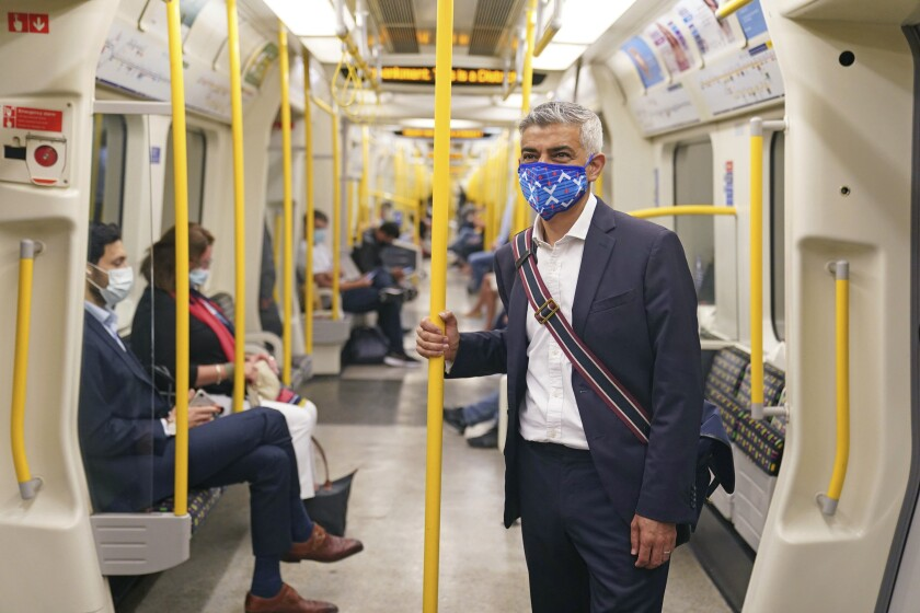 """Mayor of London Sadiq Khan wears a mask as he rides on a Circle Line tube train to visit the London Transport Museum, in London, Wednesday July 14, 2021. The London Mayor has asked Transport for London to enforce the use of mask wearing on buses and trains as a """"condition of carriage"""", even after legal restrictions in England are lifted on July 19. Khan said he was """"not prepared"""" to put tube, tram and other transport users in the capital """"at risk"""" by removing the rules on face coverings. (Kirsty O'Connor/PA via AP)"""