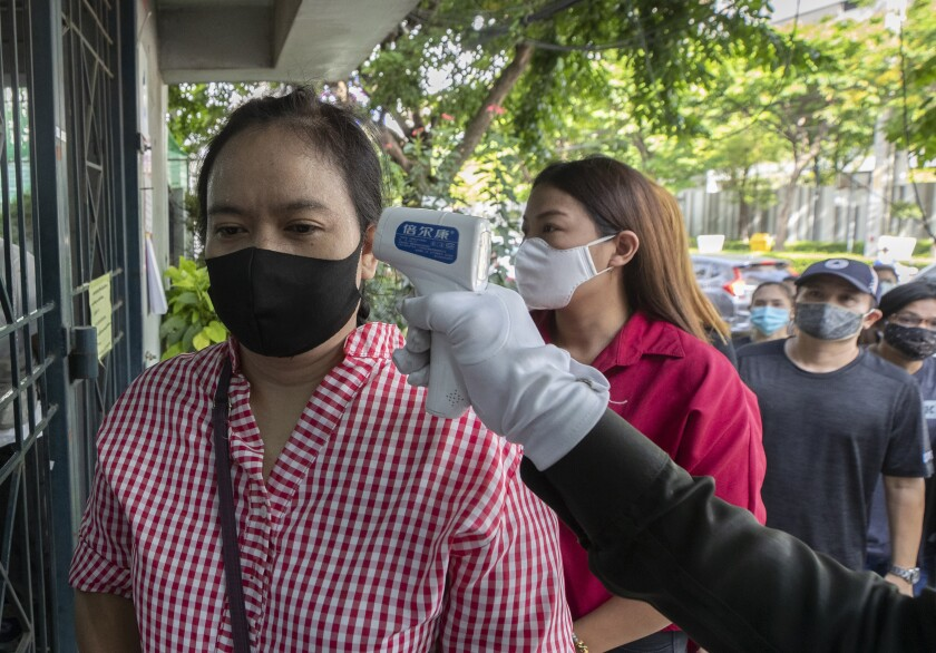 An officer checks the temperature of Wannapa Kotabin, a 38-year-old kitchen assistant at an Italian restaurant, in front of Social Security office for claim unemployment benefit in Bangkok, Thailand, Thursday, June 4, 2020. The government ordered all restaurants closed in March to combat the spread of the coronavirus, and Wannapa hasn't worked since. That's the harsh truth facing workers laid off around the world, from software companies in Israel to restaurants in Thailand and car factories in France, whose livelihoods fell victim to a virus-driven recession that's accelerating decline in struggling industries and upheaval across the global workforce. (AP Photo/Sakchai Lalit)