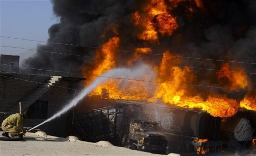 A Pakistani fire fighter tries to extinguish burning oil tankers after militants attacked a terminal in Quetta, Pakistan on Wednesday, Oct. 6, 2010. Gunmen in southwestern Pakistan torched a dozen tankers carrying fuel to NATO troops and killed a driver Wednesday, police said, the latest strike against supply convoys heading for Afghanistan since Pakistan shut a key border crossing last week. (AP Photo/Arshad Butt)