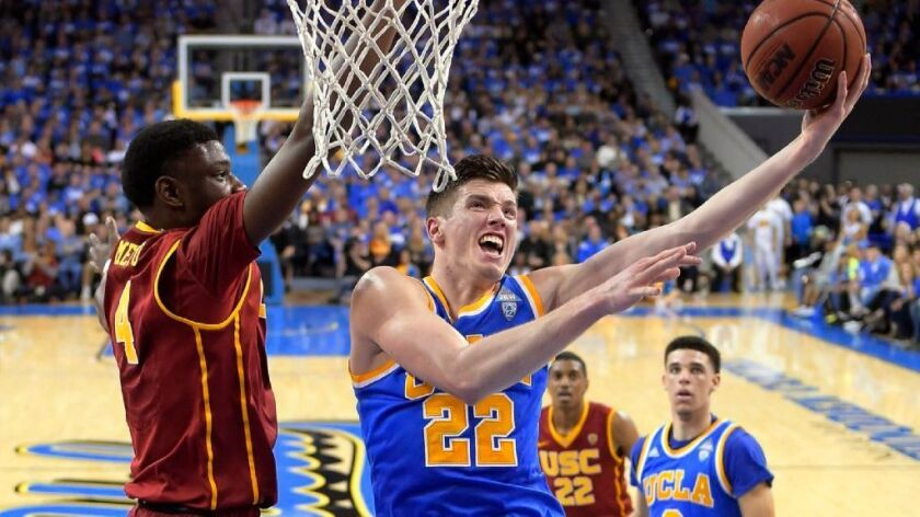 UCLA forward TJ Leaf, right, shoots as USC forward Chimezie Metu defends during the first half of a game at Pauley Pavilion on Feb. 18.