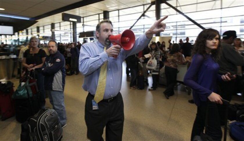 Jim McBarron, manager of station perations for Alaska Airlines, uses a bullhorn to try and find passengers for a flight that was about to take off for San Diego, Monday, Oct. 8, 2012, during a system-wide outage of the computers the airline uses to check in passengers at Seattle-Tacoma International Airport in Seattle. Most flights were delayed or canceled, but the airline was able to manually check in passengers for a few of its flights. (AP Photo/Ted S. Warren)