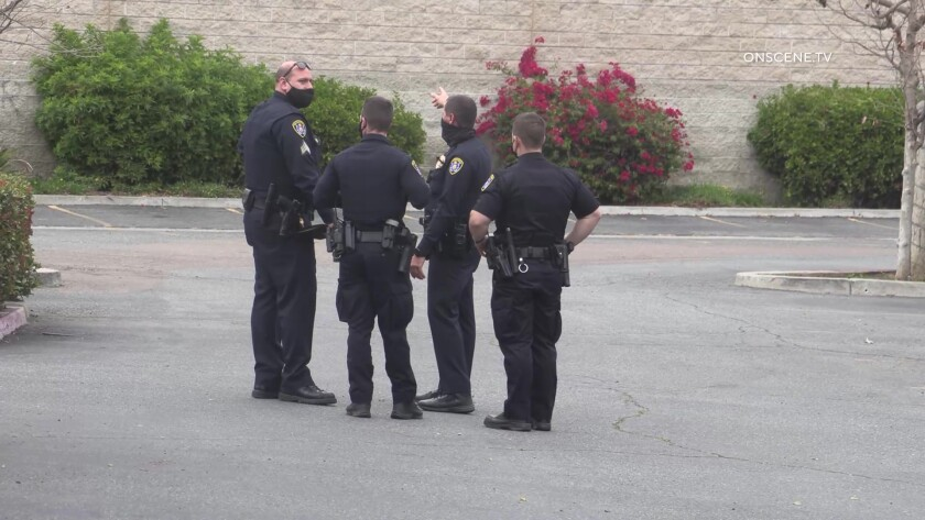 Four San Diego police officers conferring in a parking lot
