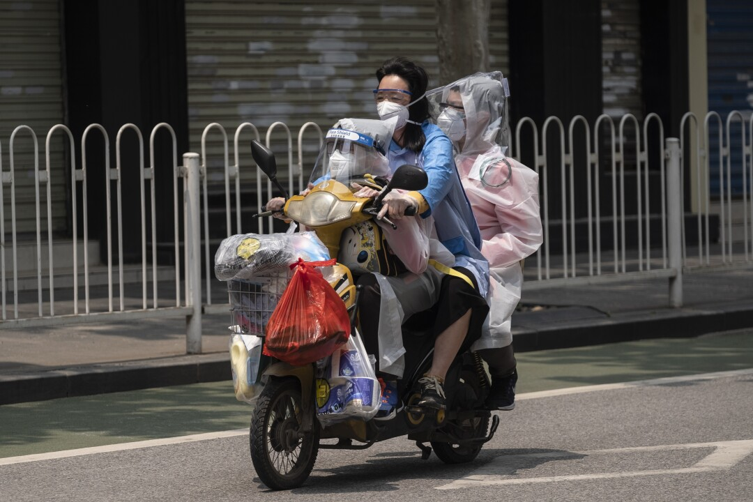 Wuhan's lockdown has lifted, but anxieties about the coronavirus remain. Travelers, above, take precautions while heading to the grocery store.