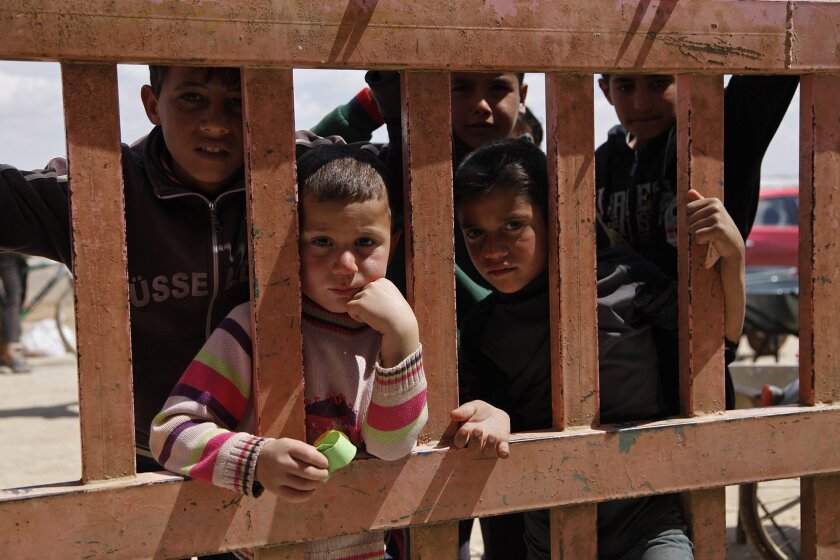 In this April 14, 2016 photo, Syrian refugees look through the gate of a grocery store at the al-Azraq refugee camp in northeast Jordan. Thousands of newly arrived Syrian refugees have been moved behind barbed wire in a separate section of the Azraq camp because Jordan considers them potential secu
