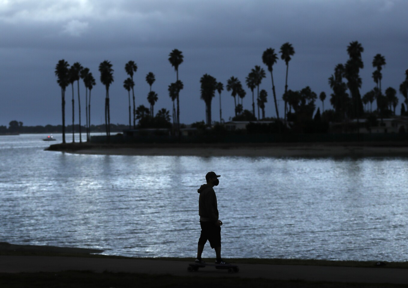 A man, wearing a mask, rides a skateboard in Mission Bay Park near De Anza Cove as the sun sets.