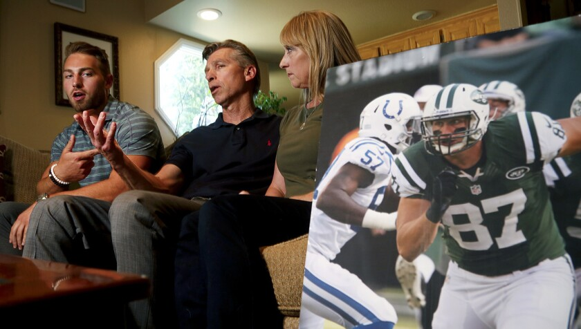 Austin, left, Ralf and Mary Reuland talk about Konrad Reuland, a former NFL tight end who died last
