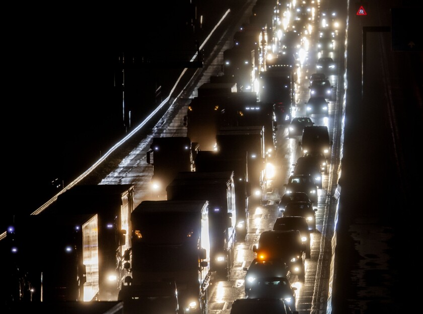Cars and trucks drive on a highway in Frankfurt, Germany, on a rainy Friday, Jan. 29, 2021. (AP Photo/Michael Probst)