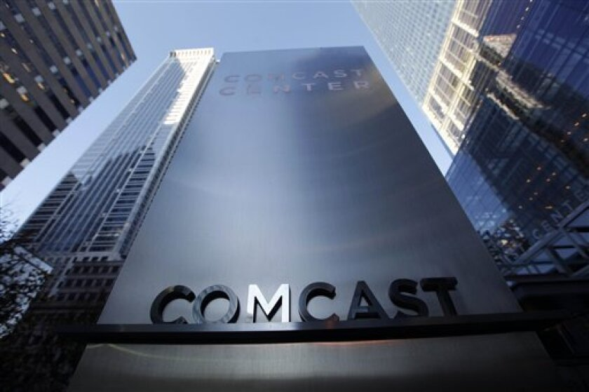 In this photo made Dec. 3, 2009, a sign outside the Comcast Center, right, is shown in Philadelphia. Higher revenue and a tax gain helped propel Comcast Corp.'s fourth-quarter earnings sharply higher Wednesday, Feb. 3, 2010, as the nation's largest cable operator solidified its position as the biggest U.S. Internet service provider as well.(AP Photo/Matt Rourke)