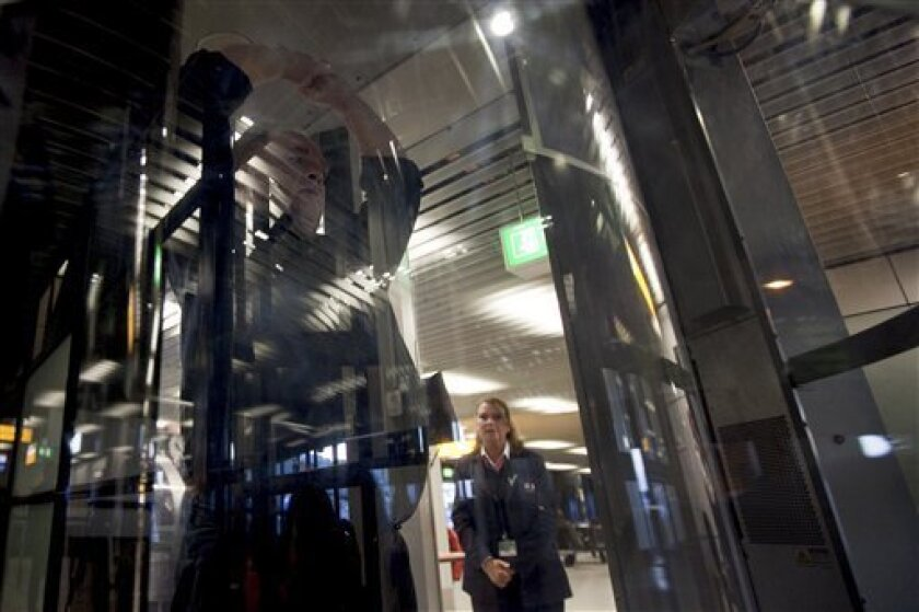 A passenger is checked inside a body scanner at Schiphol airport, Netherlands, Monday, Dec. 28, 2009. The scanners, like small walk-in closets, reveal the outline of a passenger's body to detect any concealed objects under the clothing. Body scanners that peer under a passenger's clothing might have spotted the device used in the Christmas Day attempt to blow up a Detroit-bound airliner, but American authorities have told Amsterdam's airport - where the would-be bomber went through his final security check - not to use them on U.S.-bound flights because of privacy concerns.(AP Photo/Cynthia Boll)
