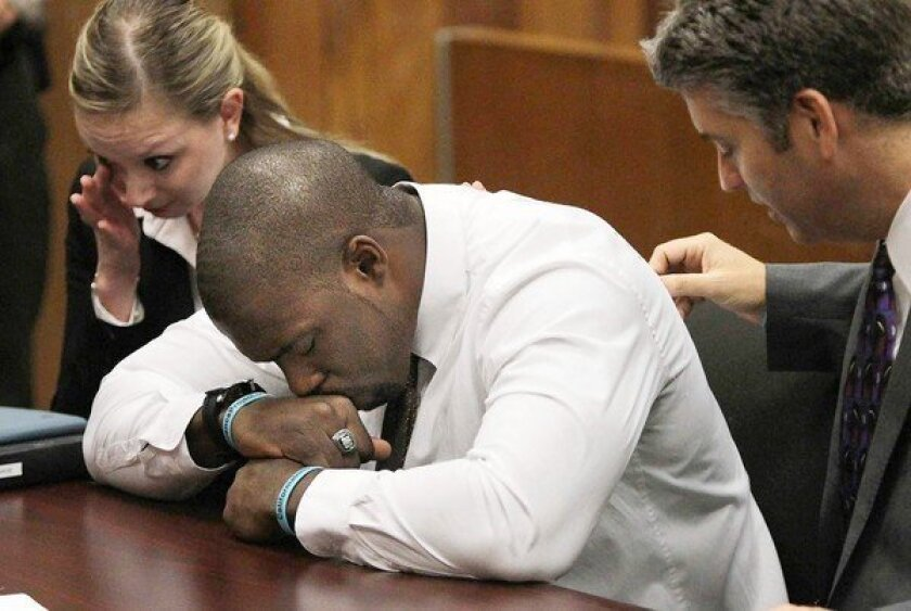 """Brian Banks, with his attorneys, is overcome with emotion in the courtroom. When he heard from the alleged victim last year, """"I stopped what I was doing and got down on my knees and prayed to God to help me play my cards right."""""""
