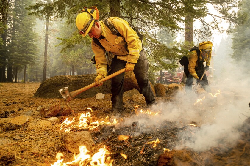 Firefighters extinguish hot spots while protecting Lake Almanor West homes from the Dixie fire