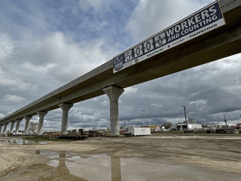 """A """"5,000 workers and counting"""" banner appears on a long, elevated structure."""