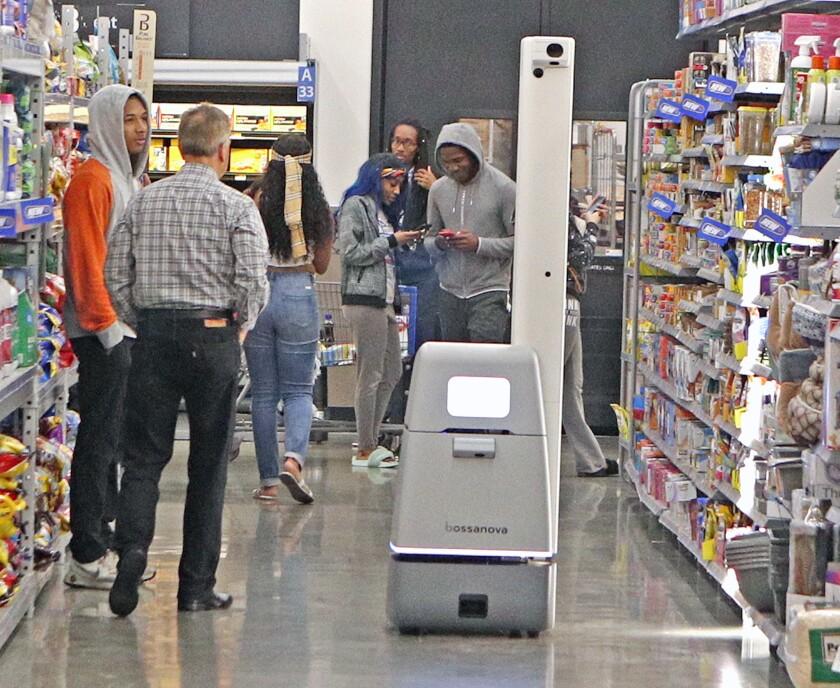 Walmart shoppers gather near a shelf-scanning robot