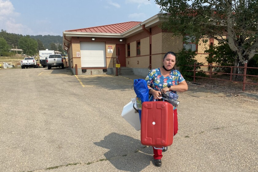 Nurse carries coolers containing vaccines