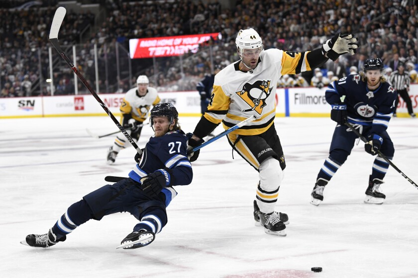 Winnipeg Jets' Nikolaj Ehlers (27) is hooked by Pittsburgh Penguins' Erik Gudbranson (44) during second-period game action in Winnipeg, Canada on Sunday.