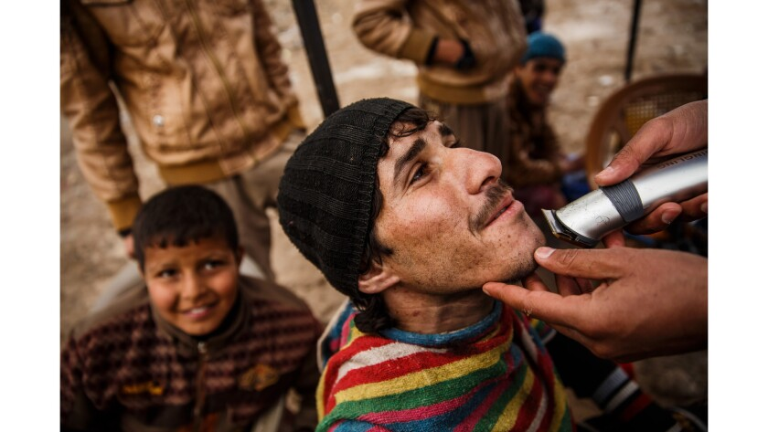 A man who identified himself as Anas, gets his beard trimmed at the United Nations camp in Hammam Alil.