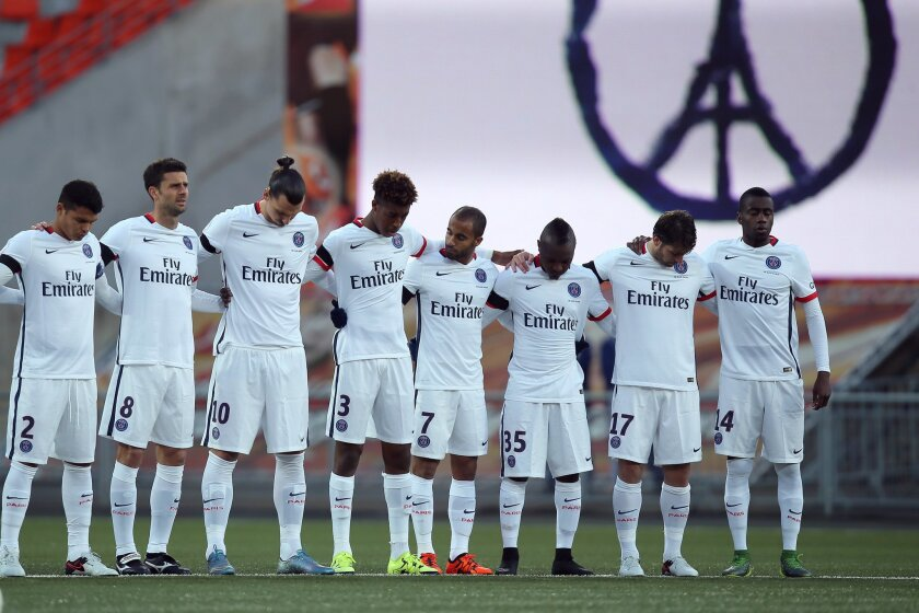 Paris Saint Germain's players observe a minute of silence in memory of the victims of the Paris attacks, at the Lorient Stadium at the start of the French League One soccer match between Lorient and Paris Saint Germain, Saturday, Nov. 21, 2015, in Lorient, western France. (AP Photo/David Vincent)
