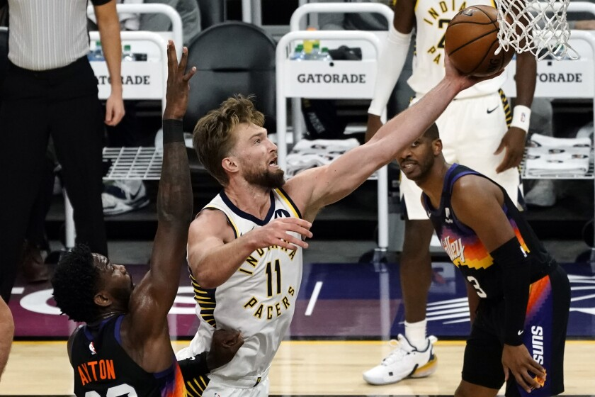 Indiana Pacers forward Domantas Sabonis (11) drives past Phoenix Suns center Deandre Ayton (22) during the first half of an NBA basketball game Saturday, March 13, 2021, in Phoenix. (AP Photo/Rick Scuteri)