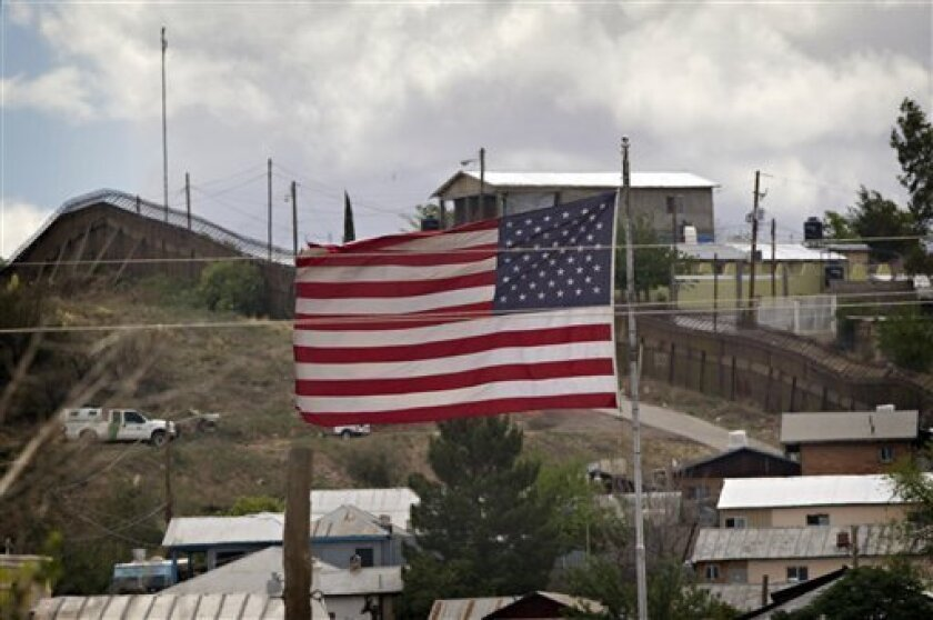 In this Thursday, April 22, 2010 photo, the American Flag flies along the international border in Nogales, Ariz. President Barack Obama will send 1,200 National Guard troops to help secure the U.S.-Mexico border, an administration official and an Arizona congresswoman said Tuesday, pre-empting Repu