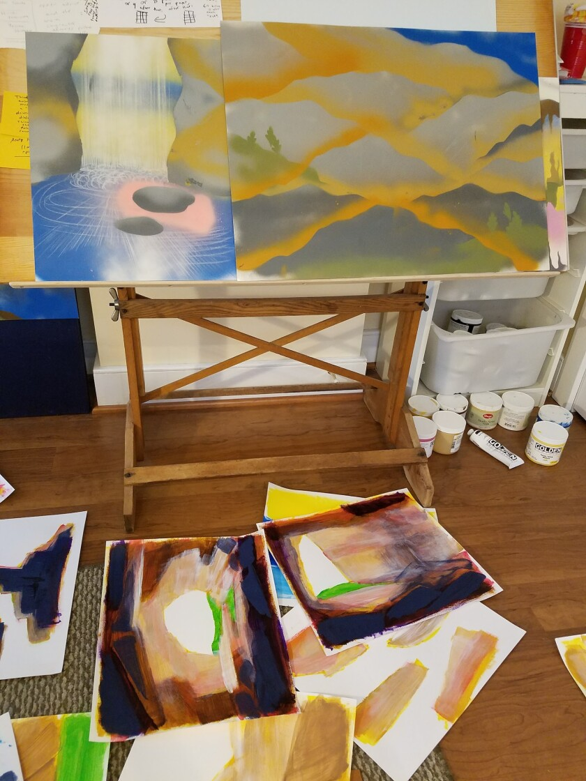 Paintings on a drawing table and the floor around it.