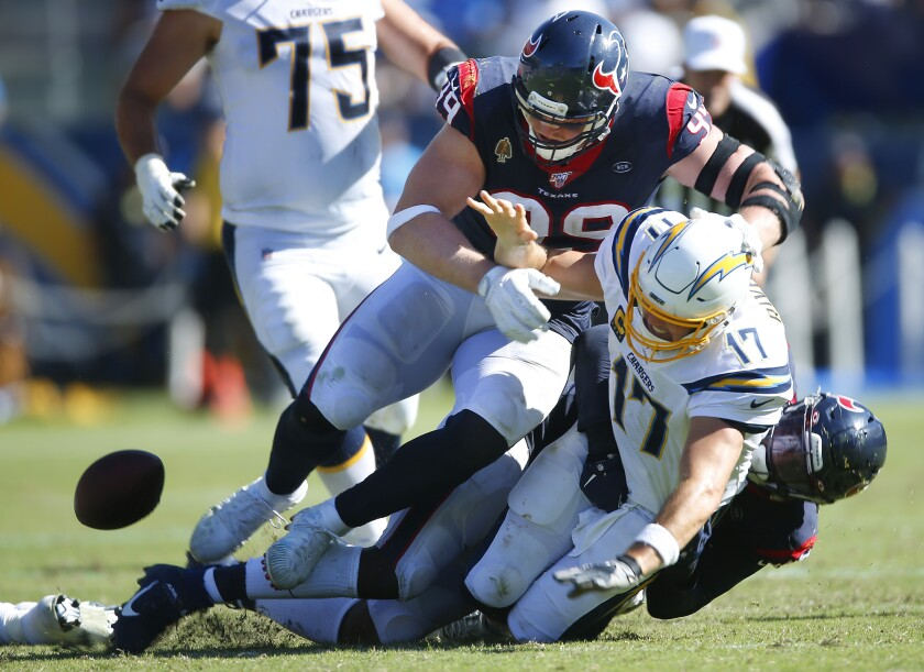 Houston Texans pass rusher Whitney Mercilus causes Chargers quarterback Philip Rivers to fumble as J.J. Watt approaches in the fourth quarter Sunday in Carson.