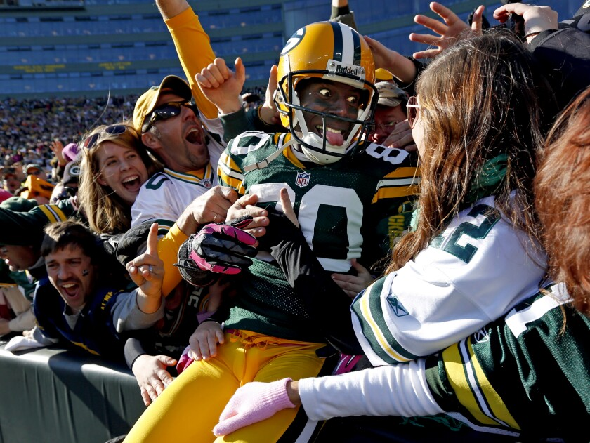 FILE - In this Oct. 28, 2012, file photo, Green Bay Packers wide receiver Donald Driver celebrates a touchdown after doing a Lambeau Leap during the second half of an NFL football game against the Jacksonville Jaguars, in Green Bay, Wisc. As lock-downs are lifted, restrictions on social gatherings eased and life begins to resemble some sense, sports are finally starting to emerge from the coronavirus pandemic. Many sports business experts believe those hardy fans will be the first to return. (AP Photo/Mike Roemer, File)