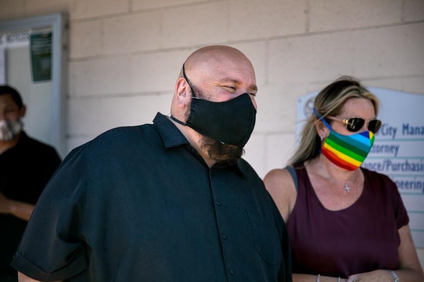 La Mesa Mayor Mark Arapostathis waits alongside a crowd to see a Pride flag hoisted.