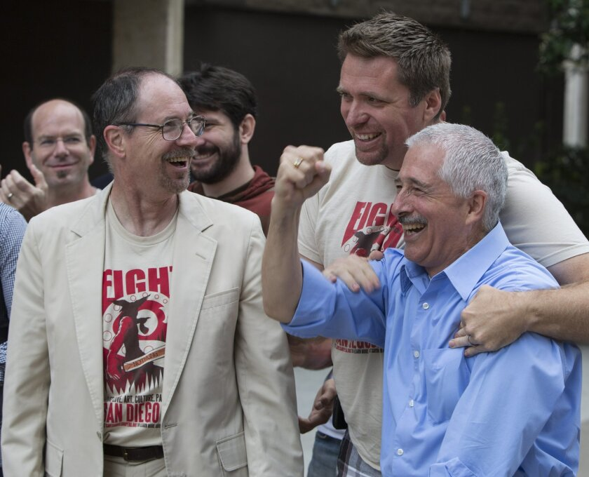 From left:  Vincent Martin, Christopher Stevens and Education Director Nicolas Reveles cheer at news that the San Diego Opera will not have to shut down.