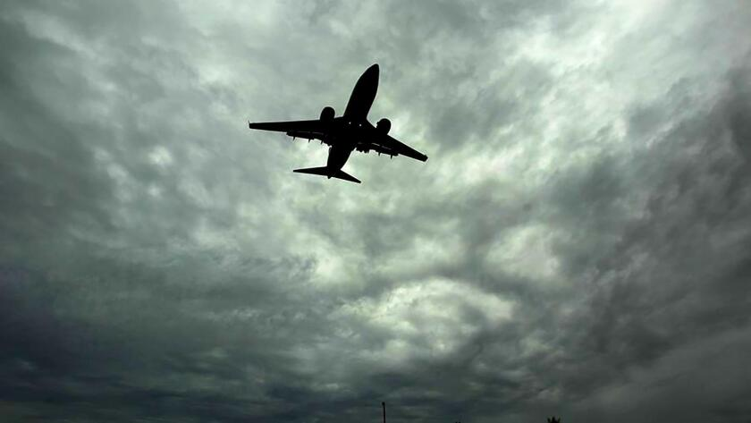An airplane lands at San Diego International Airport from the west as storm clouds fill the air.