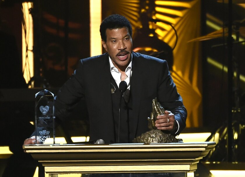 Lionel Richie accepts the Person of the Year award while holding a cast of his and his father's hand at the MusiCares Person of the Year tribute at the Los Angeles Convention Center on Saturday, Feb. 13, 2016. (Photo by Chris Pizzello/Invision/AP)