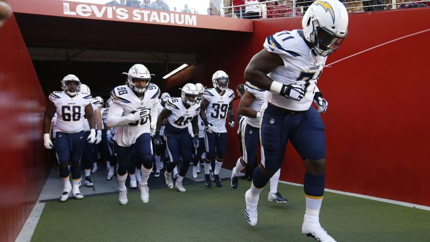 Los Angeles Chargers players run onto the field before an NFL preseason football game against the Sa