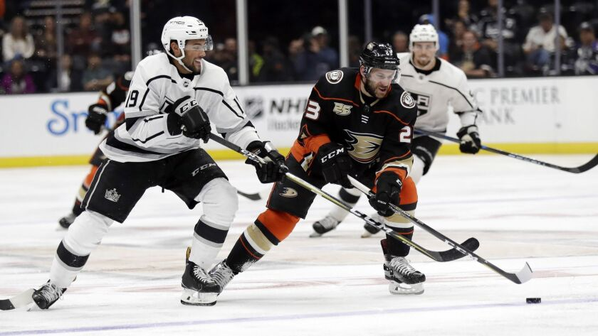 Ducks' Brian Gibbons (23), center, is defended by Kings' Alex Iafallo during the second period of a preseason game on Wednesday in Anaheim.