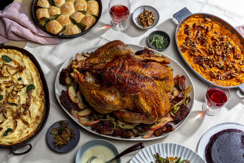 A roasted turkey surrounded by side dishes on the Thanksgiving 2020 table