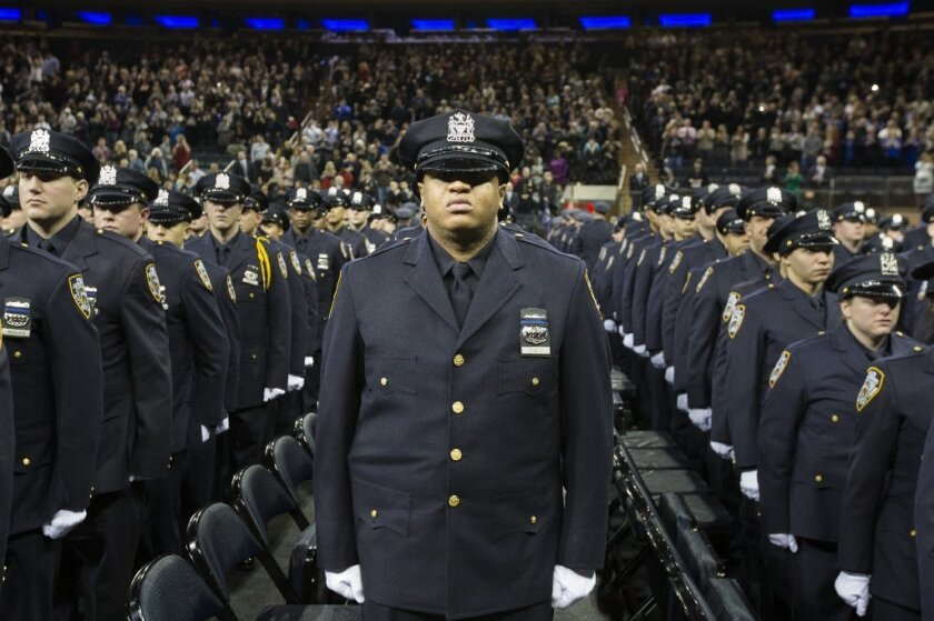 Hundreds of new NYPD recruits stand at attention at a ceremony Monday. They wore black bands over their badges in honor of officers Rafael Ramos and Wenjian Liu, who were slain Dec. 20 by a gunman who had posted anti-police rants online.
