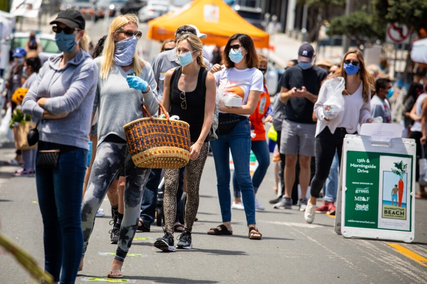 Masked visitors attend the reopening of a farmers market May 12 in Manhattan Beach. The market was closed for eight weeks due to the coronavirus.