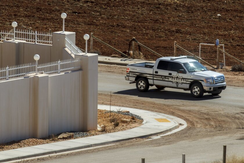 FILE - In this Feb. 18, 2013, file photo, a Marshal with the FLDS Hildale/Colorado City Town Marshals patrols along the walls of a compound built for imprisoned leader Warren Jeffs in Hildale, Utah. Two polygamous towns on the Arizona-Utah line are vigorously opposing a bid to disband their shared