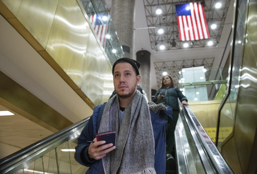 Martín Batalla Vidal takes an escalator into the Port Authority Bus Terminal in New York to take a bus to Washington, Monday, Nov. 11, 2019. Vidal is a lead plaintiff in one of the cases to preserve the Obama-era program known as Deferred Action for Childhood Arrivals and has seen his name splashed in legal documents since 2016, when he first sued in New York. His case will be heard at the Supreme Court beginning Tuesday. (AP Photo/Mark Lennihan)