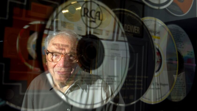 Milt Okun, founder of Cherry Lane Music Group, reflected in the framed CDs of John Denver, one of the many recording artists he shaped.