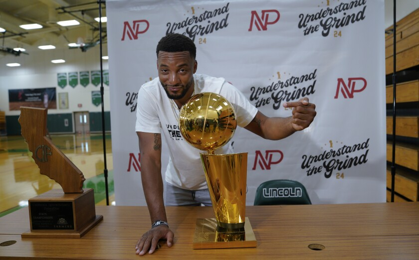 Toronto Raptors and San Diego native Norman Powell before hosting a meet and greet at his alma mater Lincoln High School on Thursday hams it up with the Larry O'Brien Trophy signifying an NBA championship.